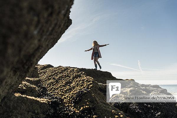 Frankreich  Halbinsel Crozon  Teenager-Mädchen  das an der Küste auf Felsen läuft
