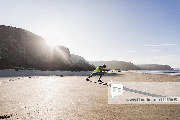 Frankreich  Halbinsel Crozon  sportlicher junger Mann  der sich am Strand ausstreckt