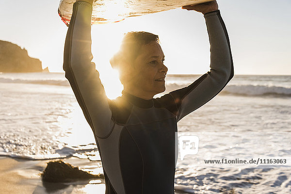 Frankreich  Bretagne  Halbinsel Crozon  Frau am Strand bei Sonnenuntergang mit Surfbrett
