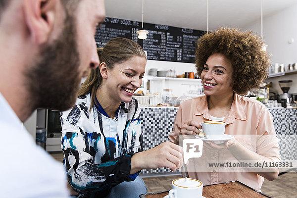 Drei Freunde treffen sich in einem Cafe