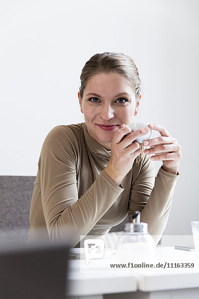 Porträt einer lächelnden jungen Frau mit Tasse im Café