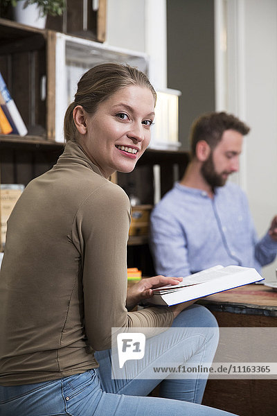 Smiling young woman with book and man in background