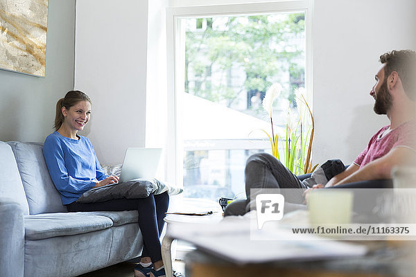 Lächelnde junge Frau mit Laptop mit Blick auf den Mann