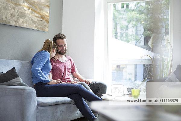 Glückliches junges Paar auf der Couch sitzend