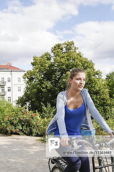 Junge Frau beim Fahrradfahren im Park