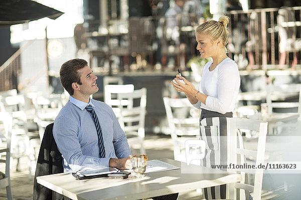 Geschäftsmann und Kellnerin im Außenrestaurant