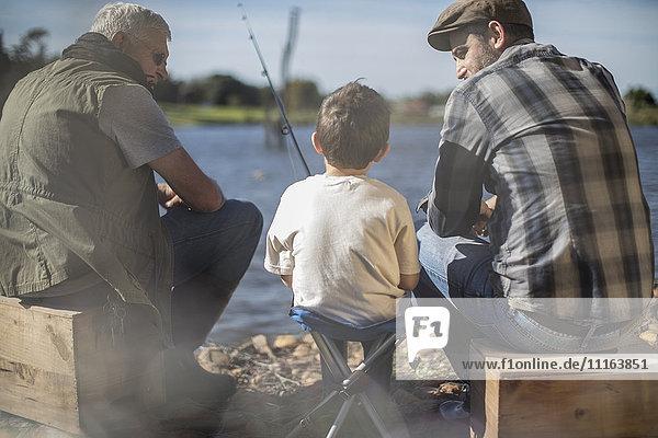 Großvater  Vater und Sohn fischen zusammen in einem See.