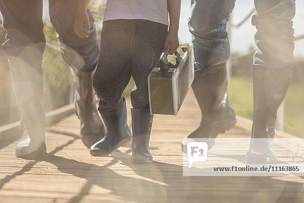 Zwei Männer und ein kleiner Junge in Gummistiefeln  die über eine Brücke mit Kiste gehen.