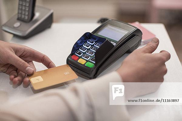 Frau mit Kreditkartenleser