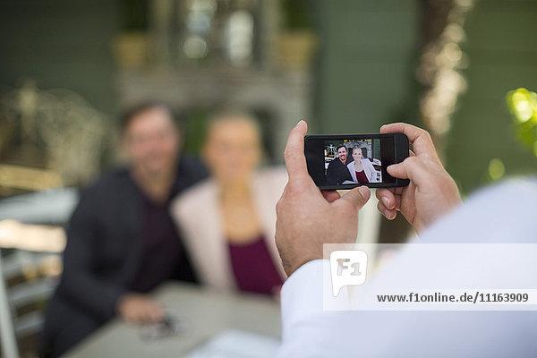 Mann  der ein Smartphone-Foto von einem Paar im Außenrestaurant macht.