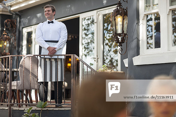 Kellner auf der Veranda mit Blick auf das Restaurant im Freien