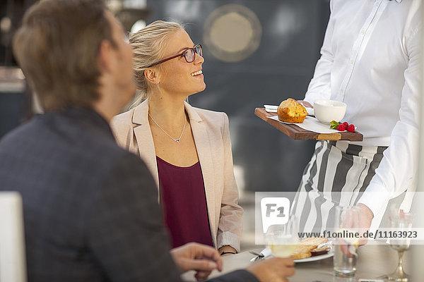 Kellner serviert Essen am Tisch für zwei Personen
