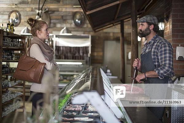 Metzger im Gespräch mit Frau in der Metzgerei