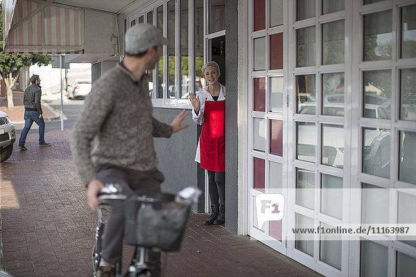Verkäuferin winkt dem Mann auf dem Fahrrad vor dem Geschäft zu.