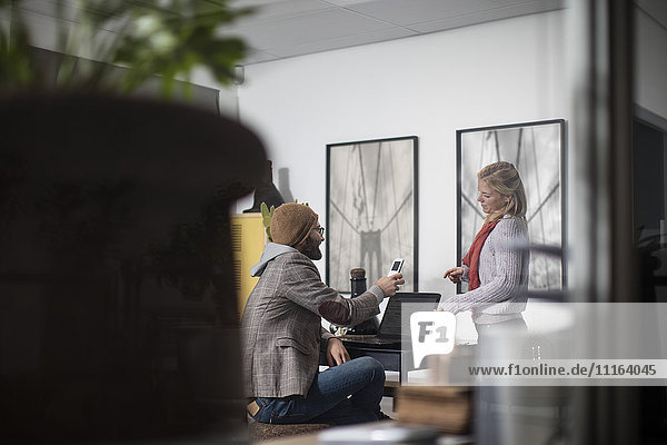 Young man and woman working together in designer office