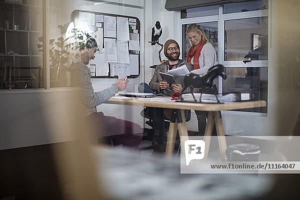 Junger Mann und Frau arbeiten zusammen im Designer-Büro