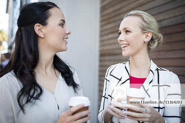 Zwei lächelnde Frauen mit Kaffee zum Mitnehmen