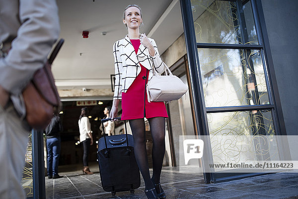 Young woman pulling suitcase out of building front door