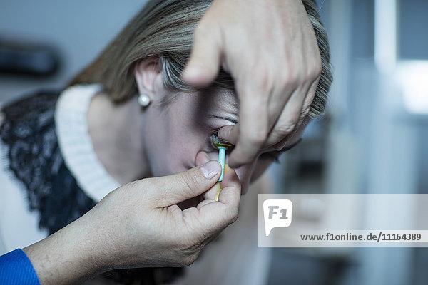 Optiker beim Einsetzen der Kontaktlinse in das Auge des Patienten