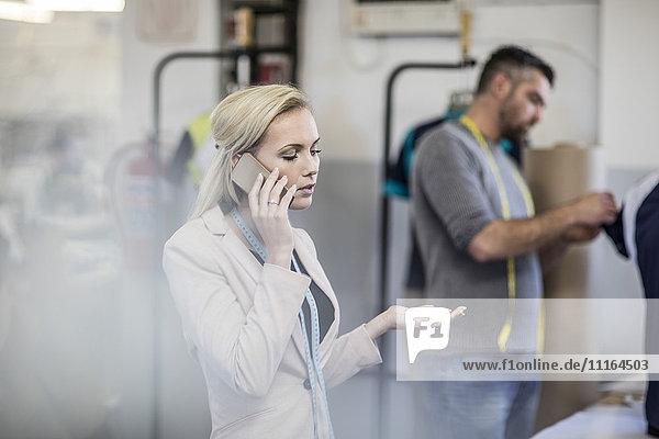 Modedesignerin am Handy in der Werkstatt