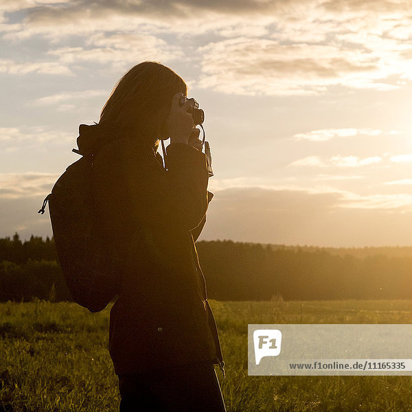 Caucasian woman photographing with camera in field at sunset