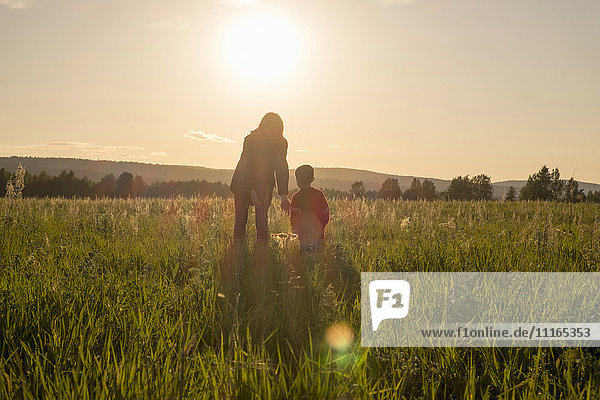 Woman and son standing in field at sunset
