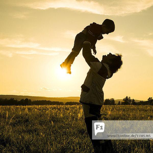 Mari man lifting son in field at sunset