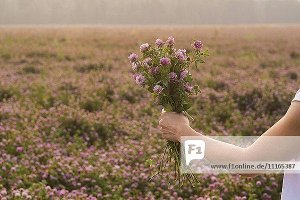 Caucasian woman holding bouquet of flowers in field