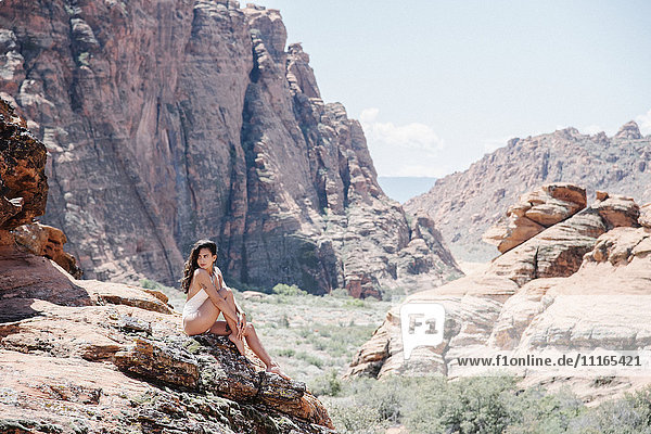 Junge Frau im weißen Badeanzug  die auf einem Felsen auf dem Canyonboden sitzt  mit Klippen und Gipfeln in der Ferne.