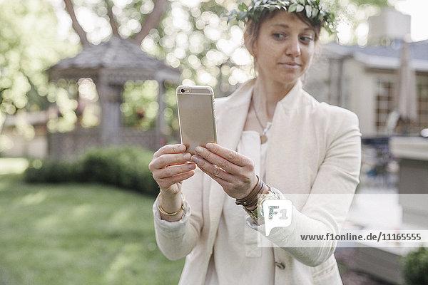 Frau mit einem Blumenkranz im Haar  die in einem Garten steht und einen Selfie mit ihrem Mobiltelefon mitnimmt.