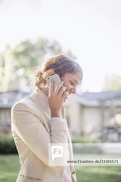 Frau  die in einem sonnenbeschienenen Garten steht und mit ihrem Handy telefoniert.