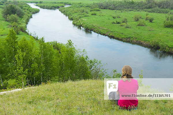 Pensive woman sitting on hill at river
