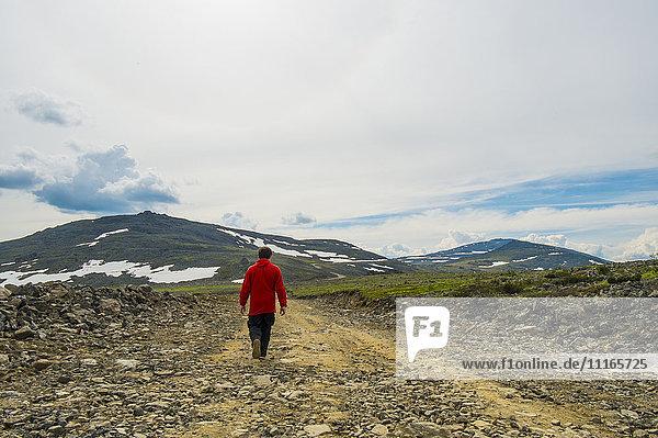 Man walking on mountain path in winter
