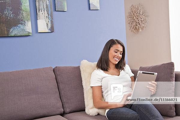 Hispanic woman sitting on sofa using digital tablet