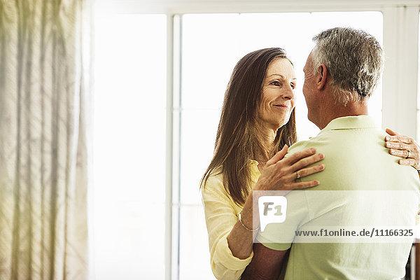 Älteres Ehepaar steht drinnen und umarmt sich.