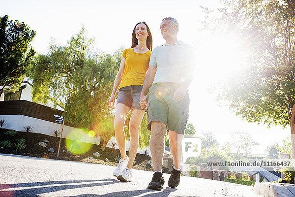 Senior couple wearing shorts walking along a street in the sunshine.