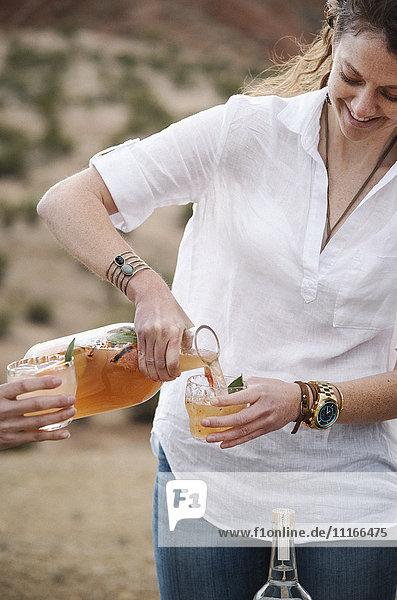Eine Frau  die in einer Wüstenlandschaft steht und ein Getränk ausschenkt.