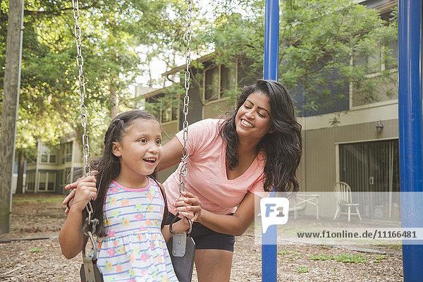 Hispanic mother pushing daughter in playground swing