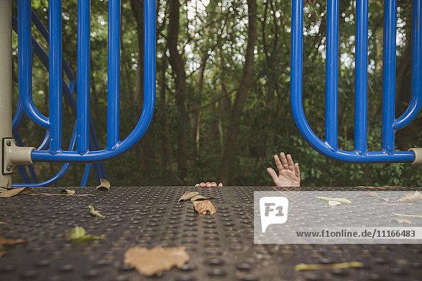 Hands of Hispanic girl reaching on playground