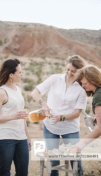 Three women standing in a desert landscape having a drink.