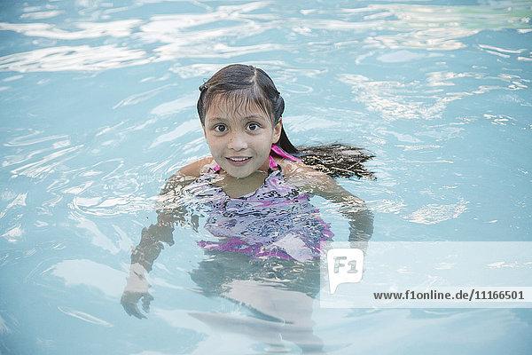 Smiling Hispanic girl in swimming pool