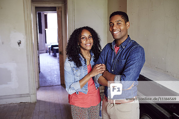 Smiling couple posing in empty house