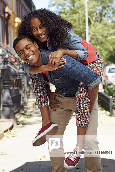 Man carrying woman piggyback on city sidewalk