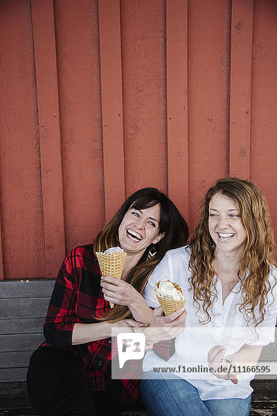 Two women sitting on a bench  eating ice cream.