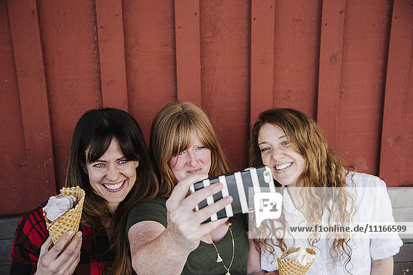 Three women eating ice cream  taking a selfie with a cell phone.