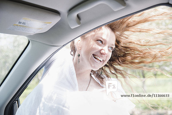 Woman on a road trip  leaning out of a car window  her long red hair blowing in the wind.