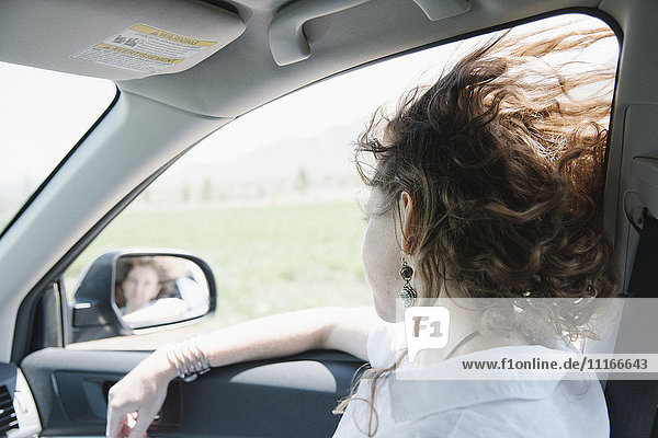 Woman in a car on a road trip  looking out of window.