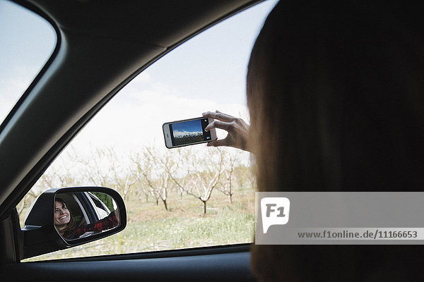 Woman in a car on a road trip  taking a picture out of the car window with a phone.
