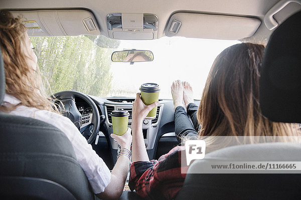 Two women in a car on a road trip  bare feet on the dashboard. View from behind.