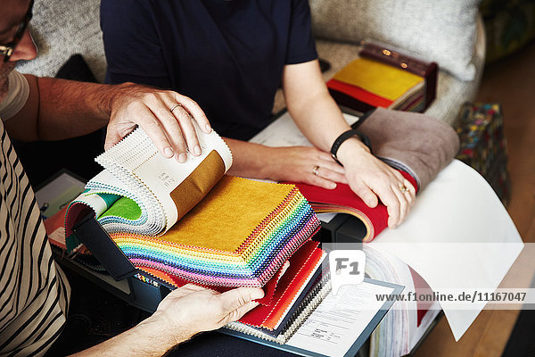 Two people sitting on a sofa  looking at a selection of fabric samples.